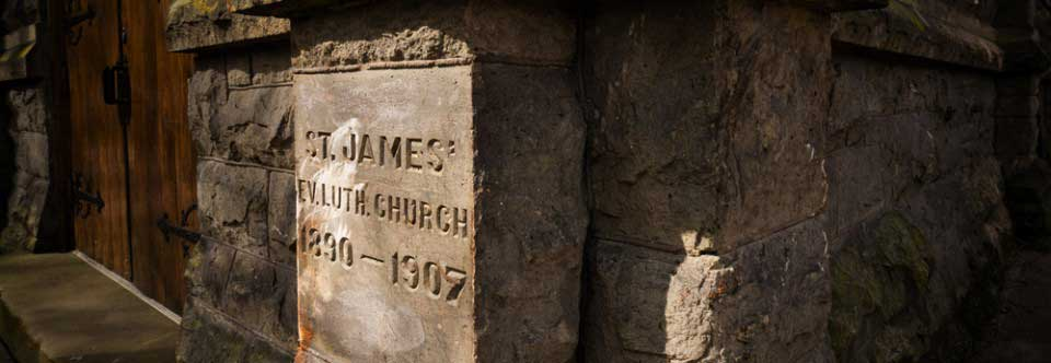 "Exterior view of the cornerstone, which reads: ""ST. JAMES' EV. LUTH. CHURCH 1890-1907"""